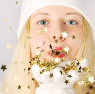 Girl blowing star shaped christmas confetti into the camera