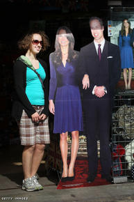 Hummmm... a tourist stands next to a cardboard cutout photograph of Prince William and Kate Middleton outside a souvenir shop.