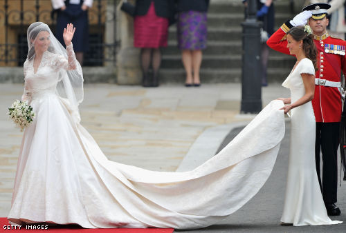 Catherine Middleton waves to the crowds as her sister and Maid of Honour Pippa Middleton holds her dress